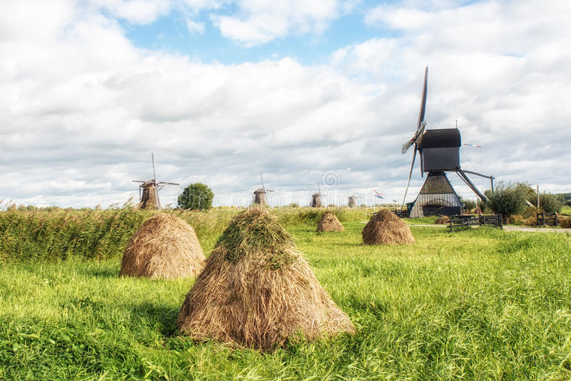Mulino a vento e mucchi di fieno fotografia stock