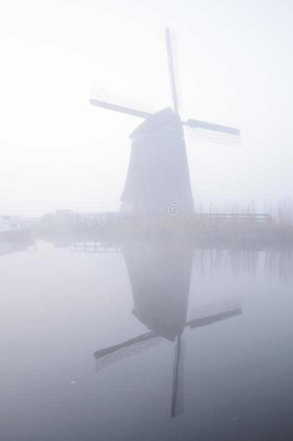 Mulino a vento e riflessione in nebbia all'alba, Paesi Bassi immagine stock libera da diritti