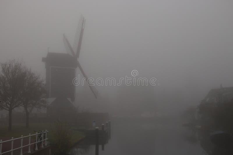 Mulino a vento in nebbia densa immagini stock