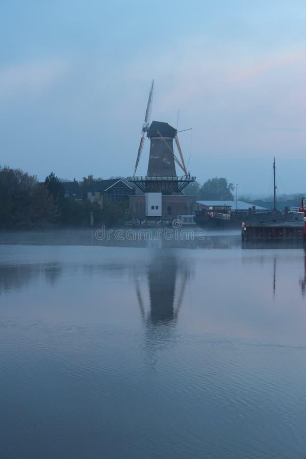 Mulino a vento nella tana aan IJssel di Nieuwerkerk lungo il fiume Hollandse IJssel in nebbia di mattina fotografia stock libera da diritti