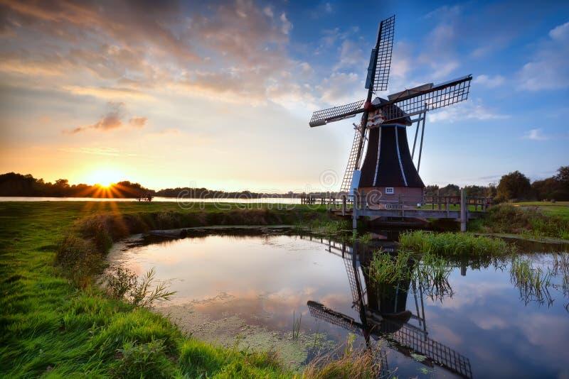 Mulino a vento olandese affascinante al tramonto fotografia stock