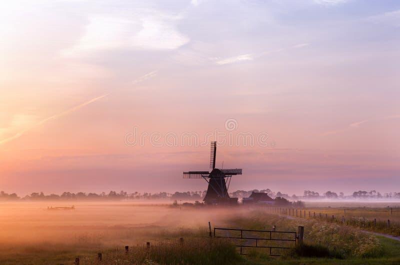 Mulino a vento olandese in nebbia in primo mattino fotografia stock