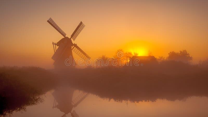 Mulino a vento olandese storico lungo un canale fotografia stock libera da diritti