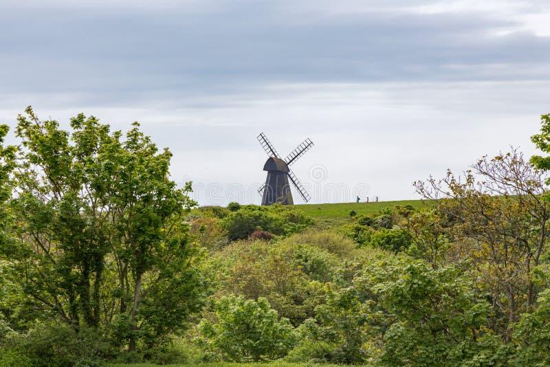 Mulino a vento sulla collina con tre viandanti sulla cresta immagine stock