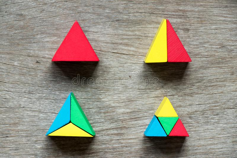 Mulit color toy block compound as triangle shape. On wood background stock image