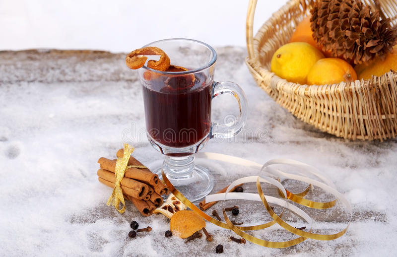 Mulled red wine on a snowy table outdoor in winter. A glass mug filled with hot mulled red wine, orange peels and spices (Gluhwein) on a snowy table royalty free stock images