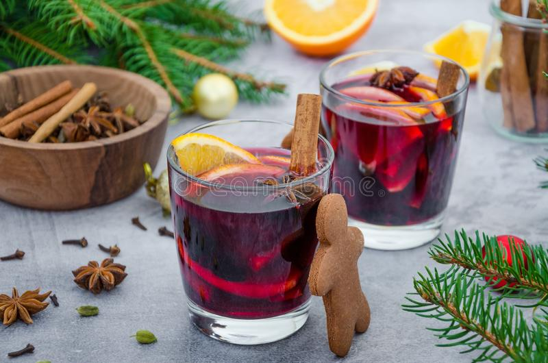Mulled wine in a glass with orange, apple, raisins, cinnamon, star anise and other spices on a gray background with gingerbread. royalty free stock image