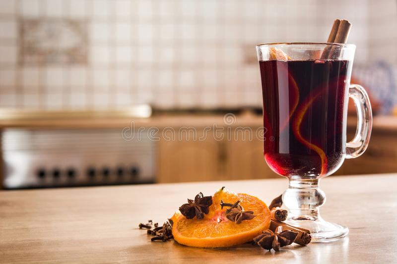 Mulled wine in glass with spice and fruit on wooden table in the kitchen. royalty free stock photos