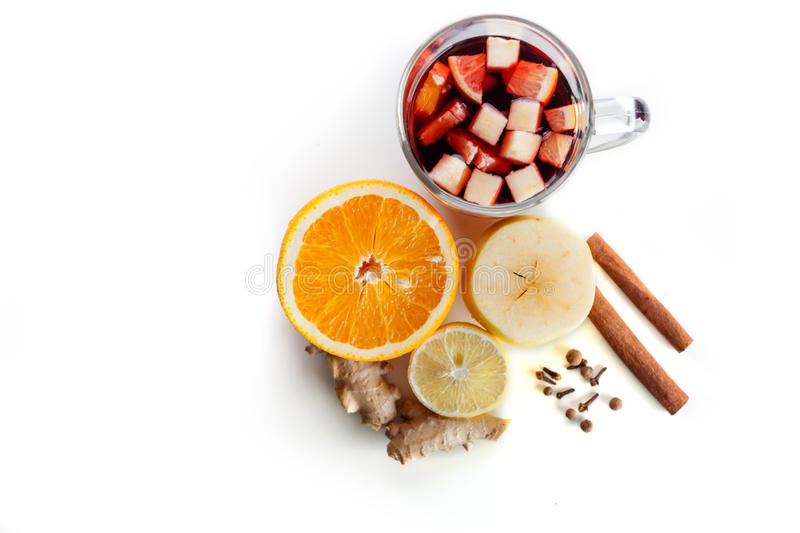 Mulled wine in a glass with spices, ginger, cinnamon and fruit on a white background stock image