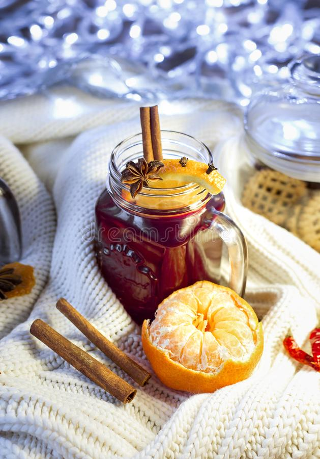 Mulled wine in a jar with orange, cinnamon sticks, anise and mandarine on a knitted sweater royalty free stock photography