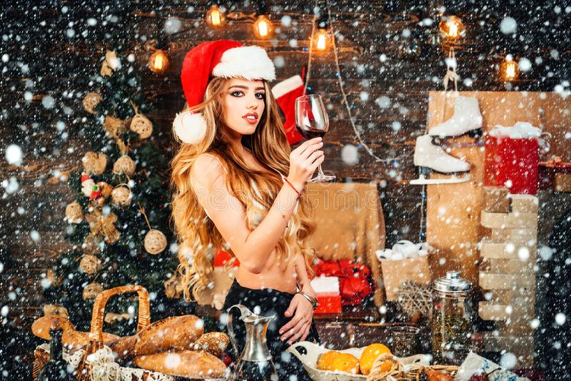 Mulled wine and red wine. Portrait of a young sexy woman. Event. Sexy girl in santa clause costume. Winter holidays and royalty free stock photos