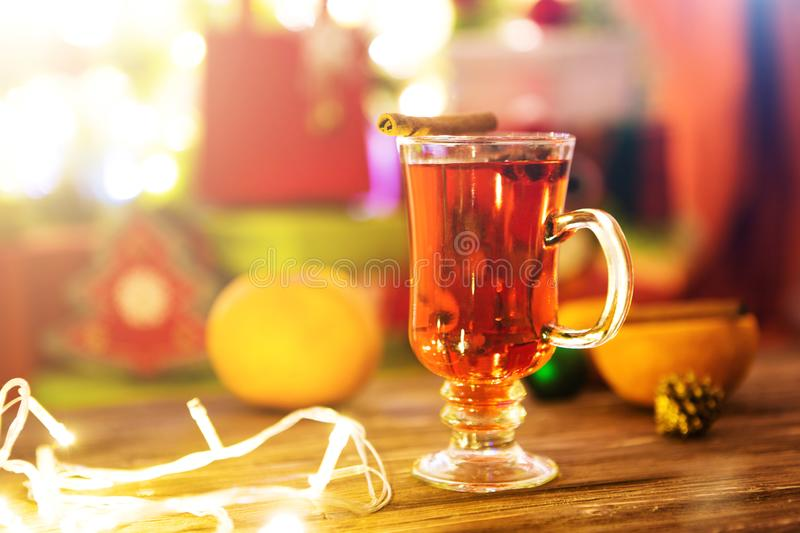 Mulled wine with spices and Christmas tree on wooden background stock photo