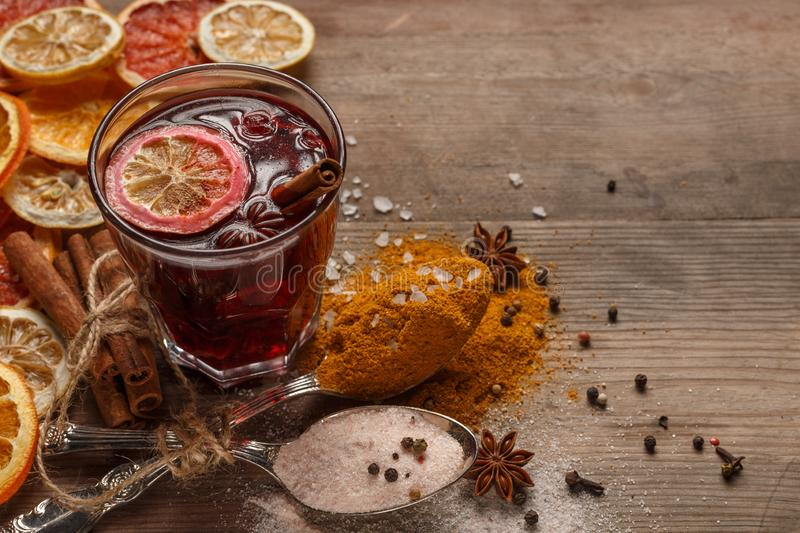 Mulled wine, spices and dried fruits on a rustic table stock photos