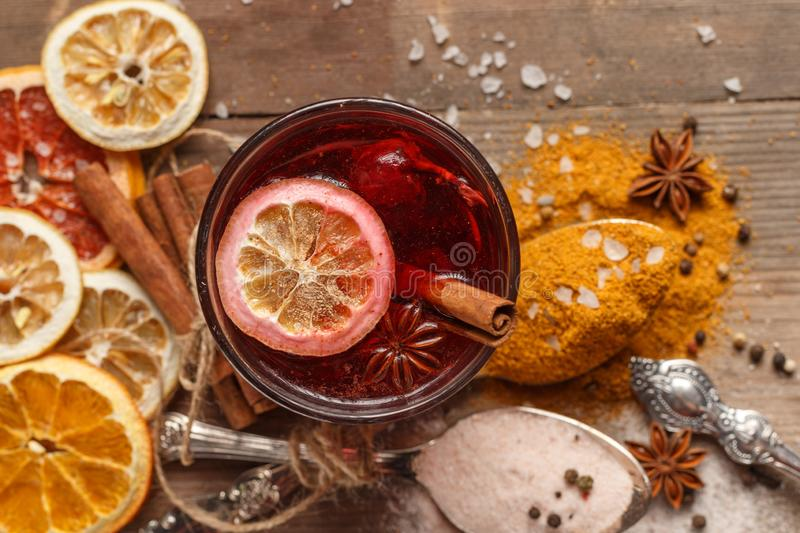 Mulled wine, spices and dried fruits on a rustic table royalty free stock photography