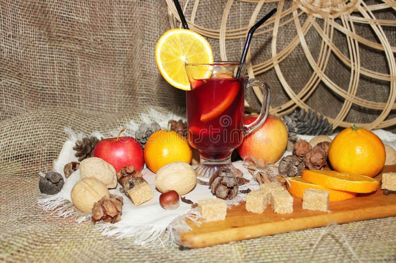 Mulled wine with spices and fruit on wooden background. Side view. stock photo