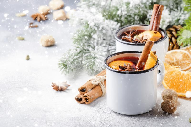 Mulled wine in white metal mugs with cinnamon, spices and orange with fir tree and christmas lights - traditional drink on winter. Holiday. Copy space for text royalty free stock photo