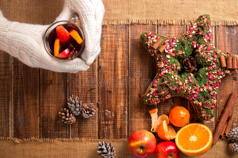 Mulled wine in woman hands in white knitted gloves near spices and fruit ingredients on wooden table. Winter warming drink. Christ royalty free stock photos