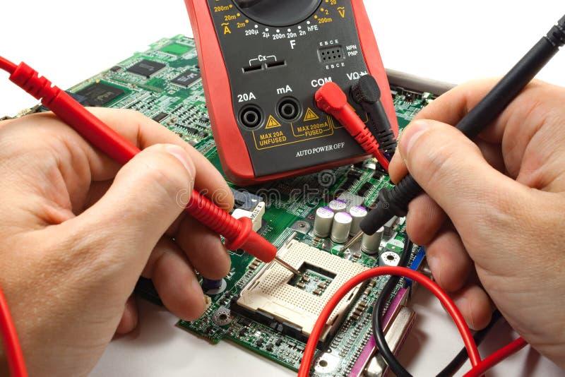 Multímetro de Digitaces con la punta de prueba en las manos del ` s del amo en un taller imagenes de archivo