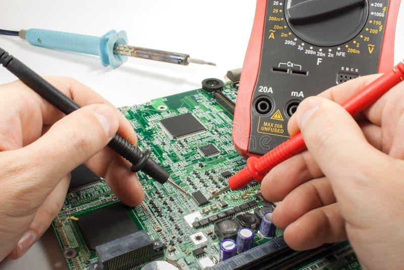 Multímetro de Digitaces con la punta de prueba y soldador en las manos del ` s del ingeniero en un taller foto de archivo