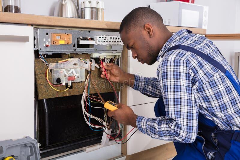 Multímetro digital de Fixing Dishwasher With do técnico fotografia de stock