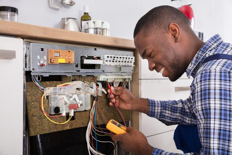 Multímetro digital de Fixing Dishwasher With do técnico imagem de stock