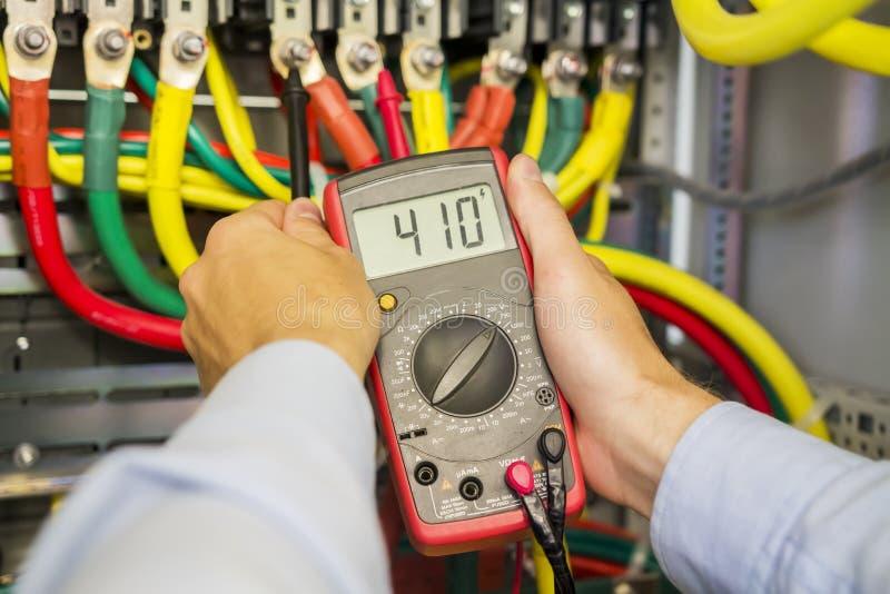 Multímetro en manos del electricista en primer de alto voltaje de la caja del circuito trifásico del poder Manos del ingeniero co imagenes de archivo