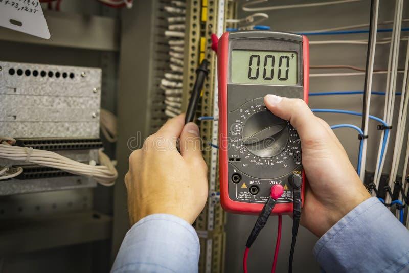 Multímetro nas mãos do close up do coordenador do eletricista no fundo bonde do painel Teste o circuito Preste serviços de manute fotos de stock