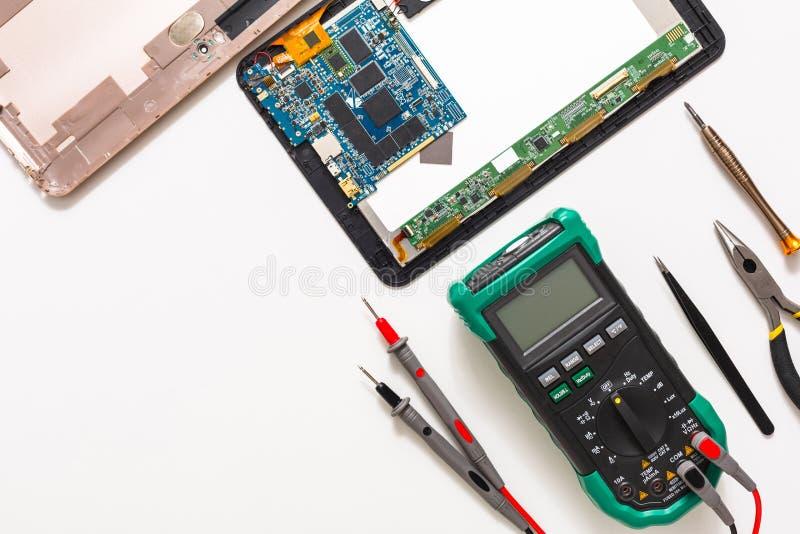 Multímetro y tableta rota, electrónica en el taller de reparaciones foto de archivo libre de regalías