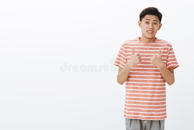 Multa que eu suponho Retrato do homem asiático atrativo novo inábil incerto em t-shirt listrado que faz o ucertain apertado sorri foto de stock royalty free