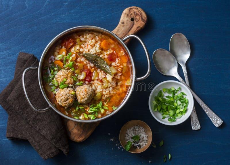 Multi зерно, фрикадельки и суп овощей в баке на голубой предпосылке, взгляд сверху Еда домашней кухни комфорта здоровая сезонная стоковая фотография