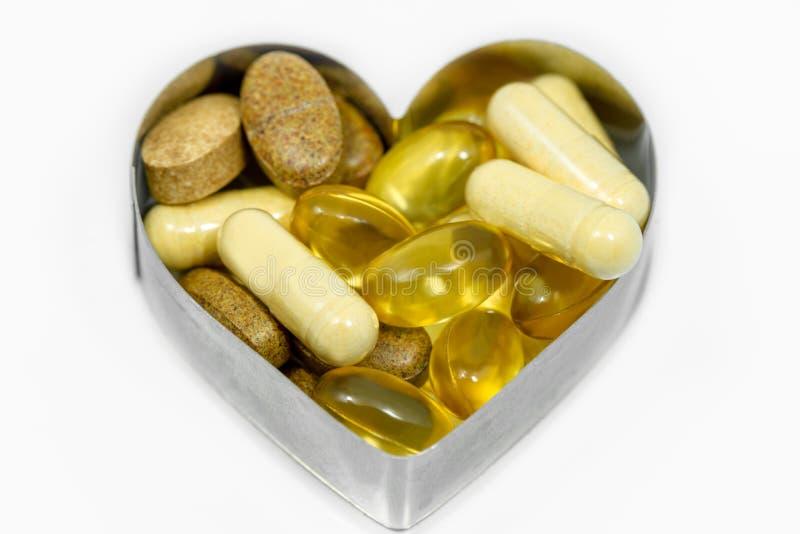 Multi пилюльки витамина в сердце стоковые фотографии rf