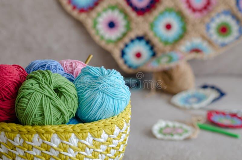 Multi покрашенное одеяло младенца и красочные пряжи на софе стоковые фотографии rf