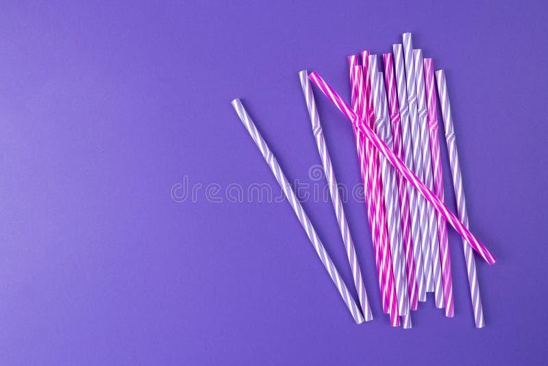 Multi покрашенные выпивая соломы на пурпурной предпосылке стоковое изображение