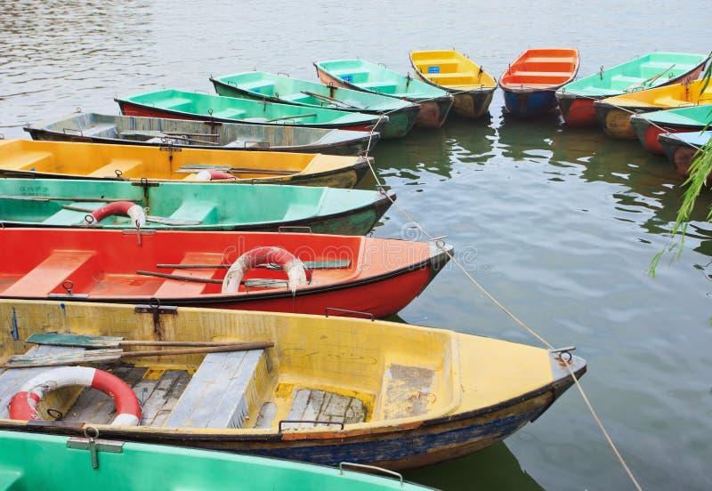 Multi покрашенные шлюпки строки причалили в озере стоковая фотография