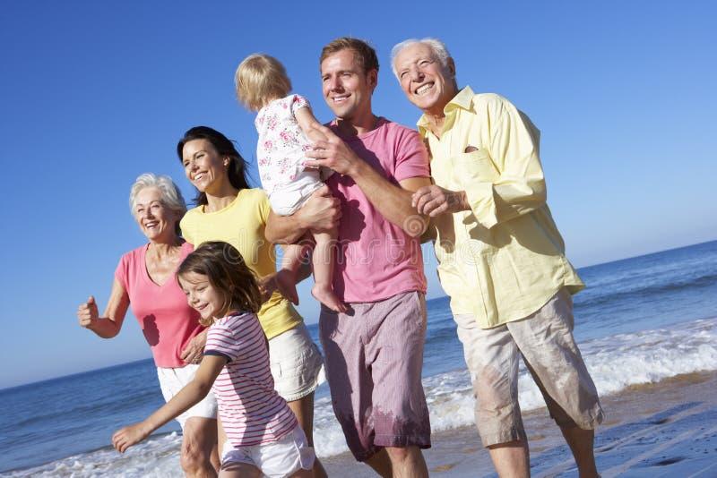 Multi семья поколения бежать вдоль пляжа совместно стоковое изображение rf