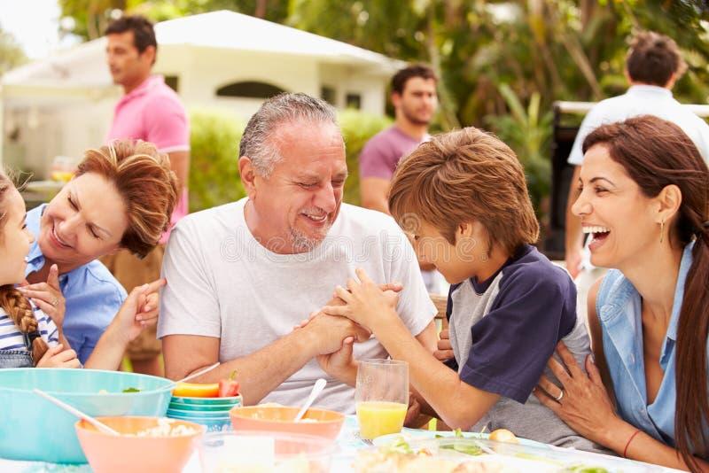 Multi семья поколения наслаждаясь едой в саде совместно стоковые фотографии rf