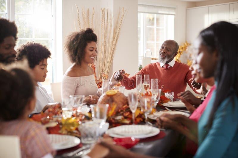 Multi семья смешанной гонки поколения держа руки и говоря грациозность перед едой на их обеденном столе благодарения, выборочным  стоковые изображения rf