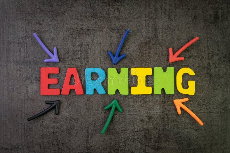Multi стрелки цвета указывая на заработок слова в центр черных стены, дохода от бизнеса или дохода доски цемента от стоковая фотография rf