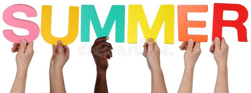 Multi этническая группа людей держа лето слова стоковое изображение