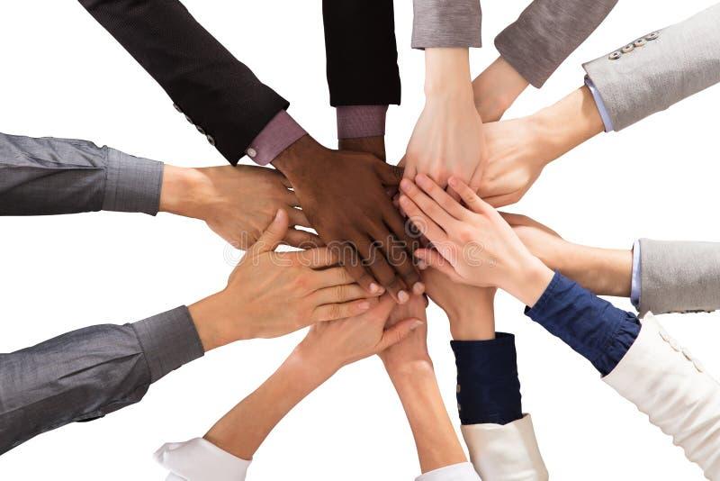 Multi этнические бизнесмены штабелируя руки стоковое изображение