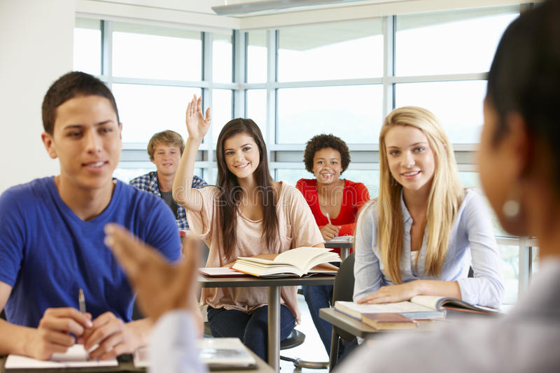 Multi alunos adolescentes raciais na classe uma com mão acima imagens de stock