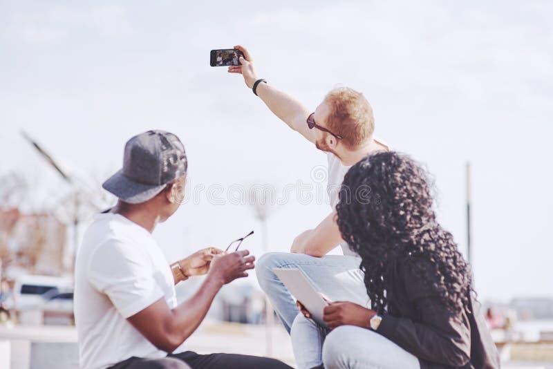 Multi amigos étnicos bonitos que usam um portátil na rua e para fazer o selphie Conceito do estilo de vida da juventude fotografia de stock