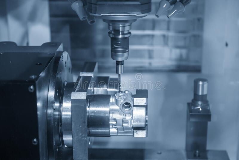The multi-axis CNC milling machine tapping the thread at the aluminium casting parts by tapping tool . The  multi-axis  CNC milling machine  tapping the thread royalty free stock photos