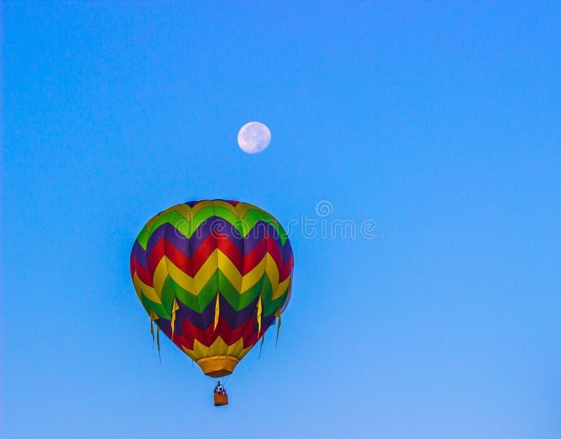 Multi balão de ar quente listrado colorido com lua acima imagem de stock