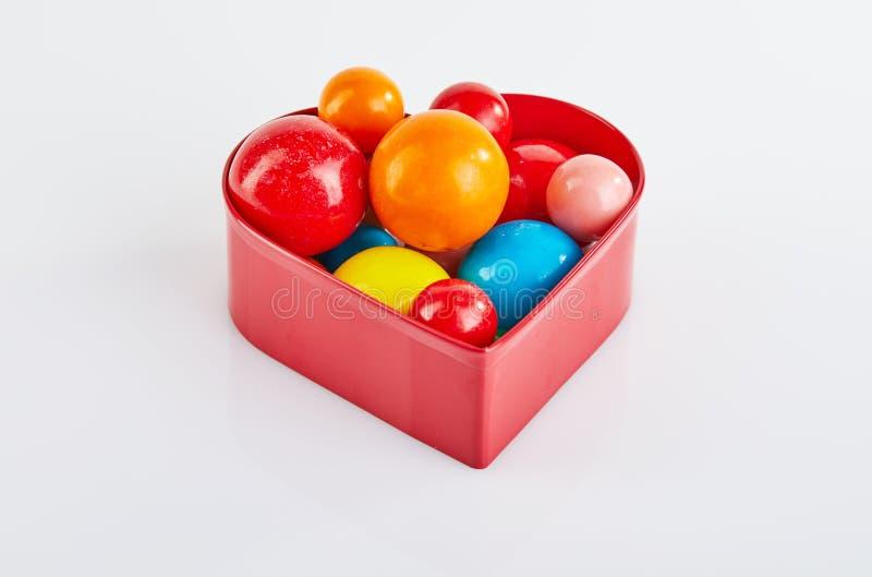 Multi bolas coloridas da pastilha elástica em um fundo branco em um coração vermelho com reflexão fotografia de stock