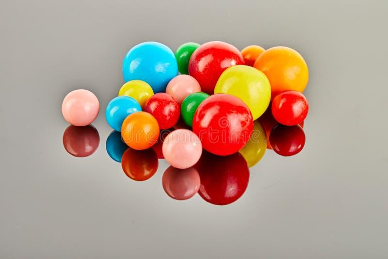 Multi bolas coloridas da pastilha elástica em um fundo cinzento com reflexão fotos de stock royalty free