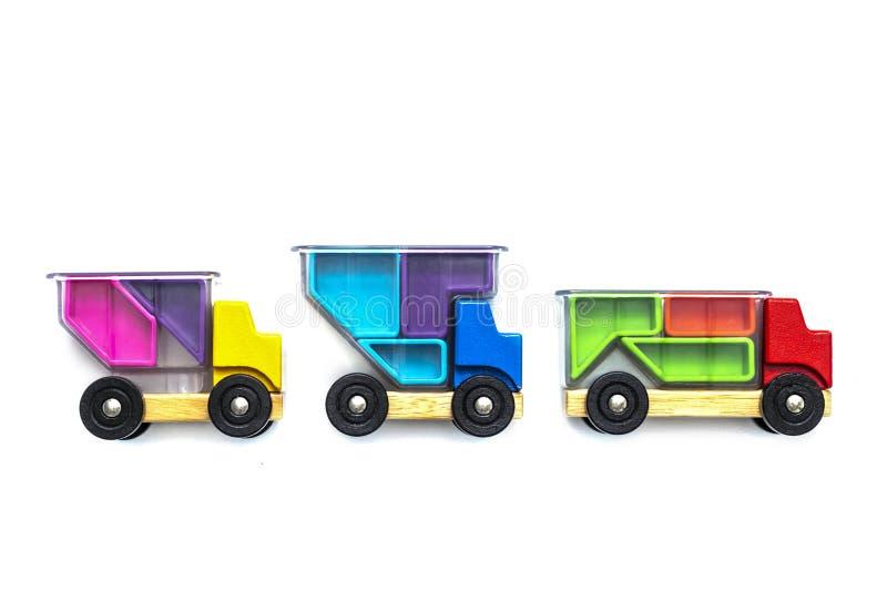 Multi caminhões coloridos dos carros do brinquedo com um corpo transparente carregado com os blocos - enigmas em um fundo branco  imagens de stock