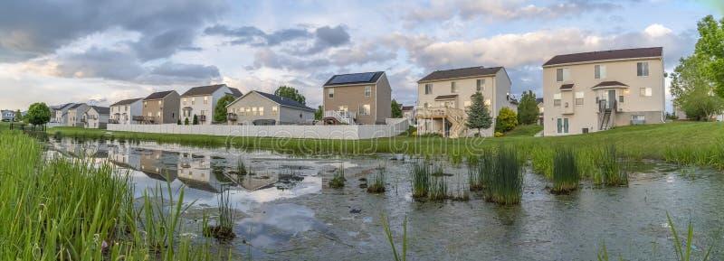 Multi casas bonitas do andar construídas na frente de uma lagoa gramínea e brilhante imagens de stock royalty free