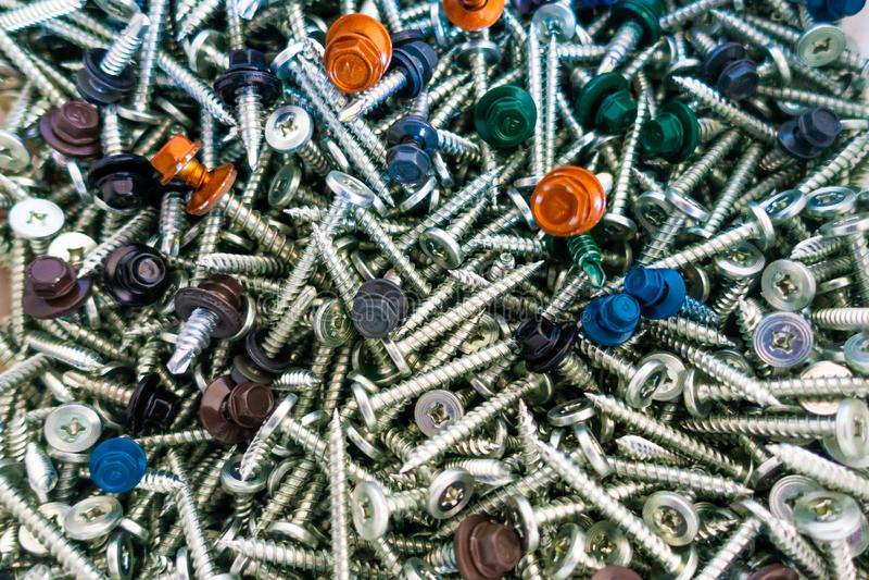 Multi coloré couvrir visse sur une pile des vis argentées de toiture image stock