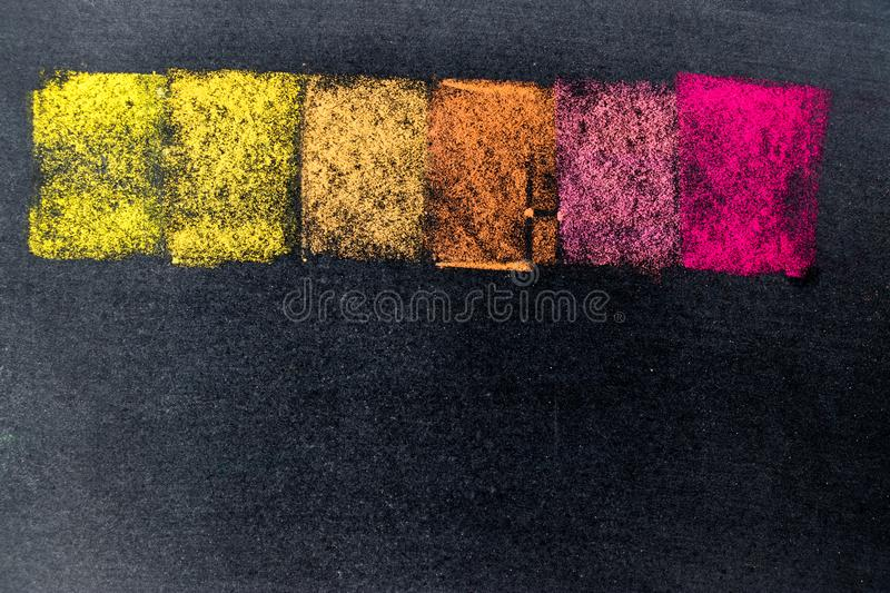 Multi color chalk drawing as striped line on black board stock photography